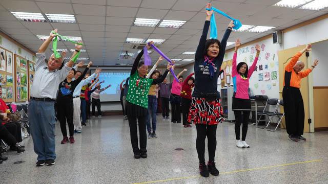 文創社老師帶領學員示範用彈力帶做健康操。